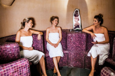 Drei Frauen sitzen in lilafarbener Dampfsauna mit Kristall